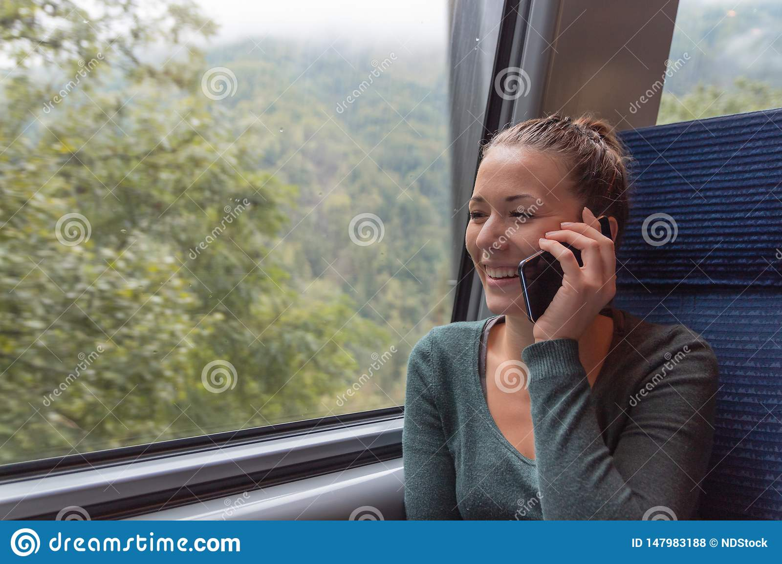Young woman phoning with his smartphone during a journey in the train while she is going to work