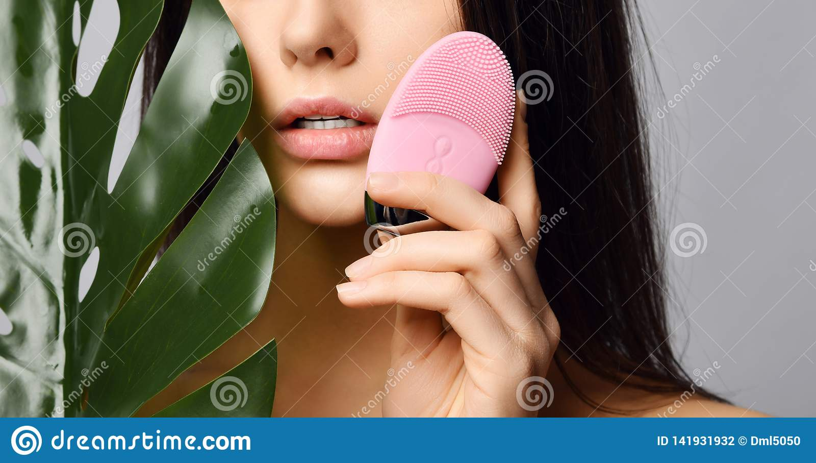 Young woman with pink face exfoliator brush silicone cleansing device for sensitive normal skin with tropical palm leaf on gray