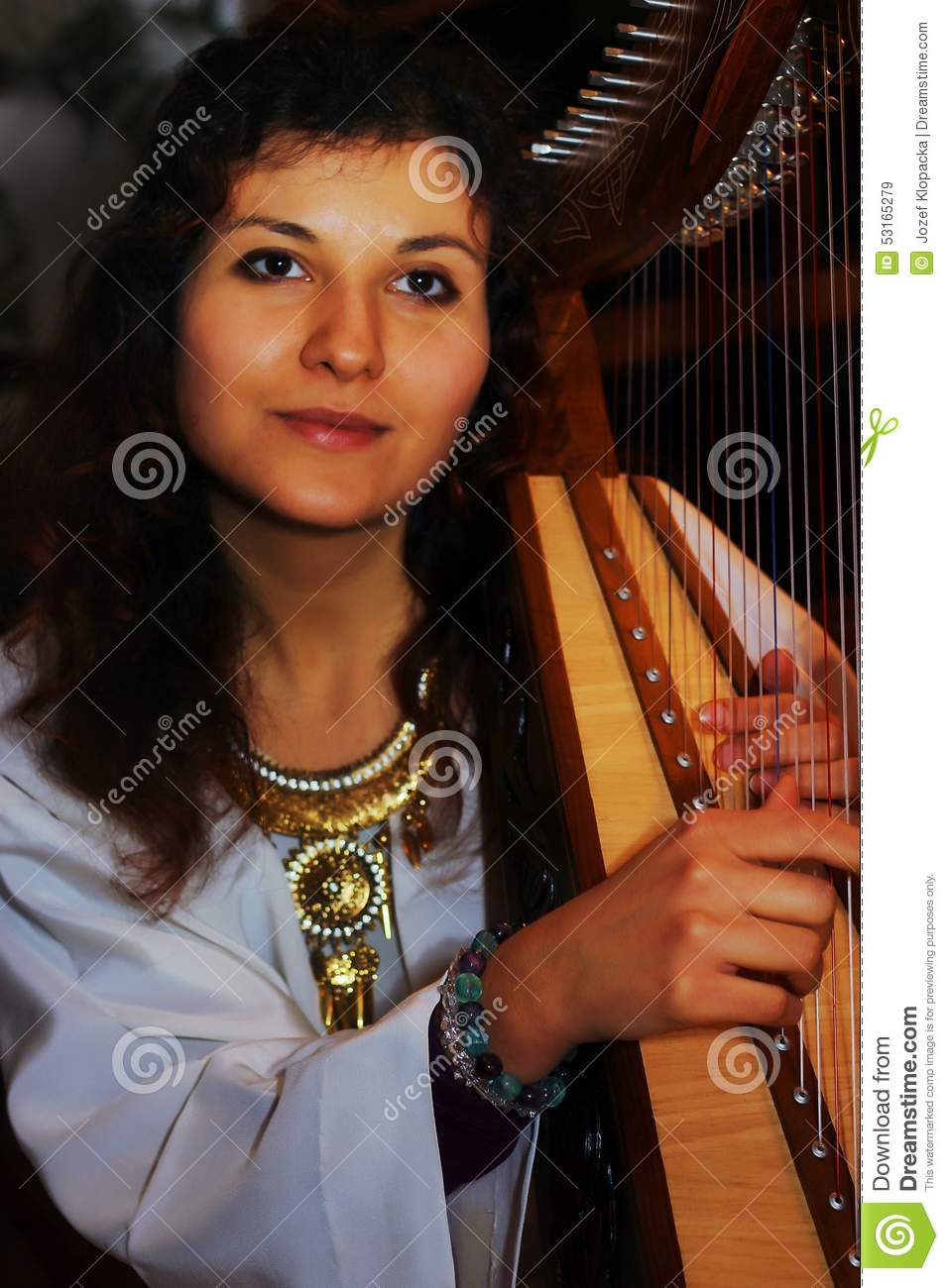 Young Woman Playing Celtic Harp In A White Angelic