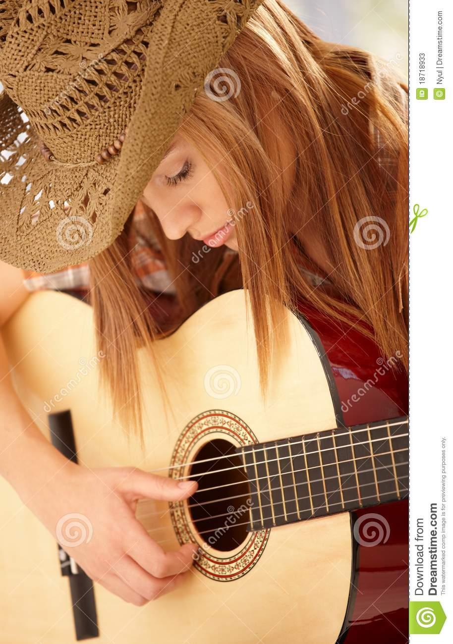 Young woman playing guitar with expression