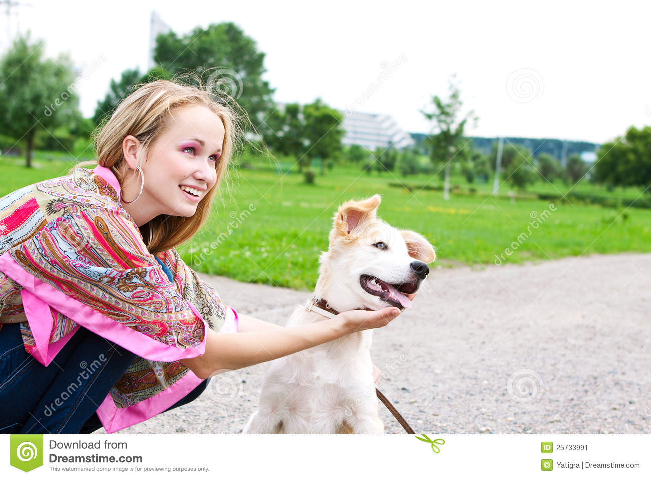 Young woman playing with puppy outdoor