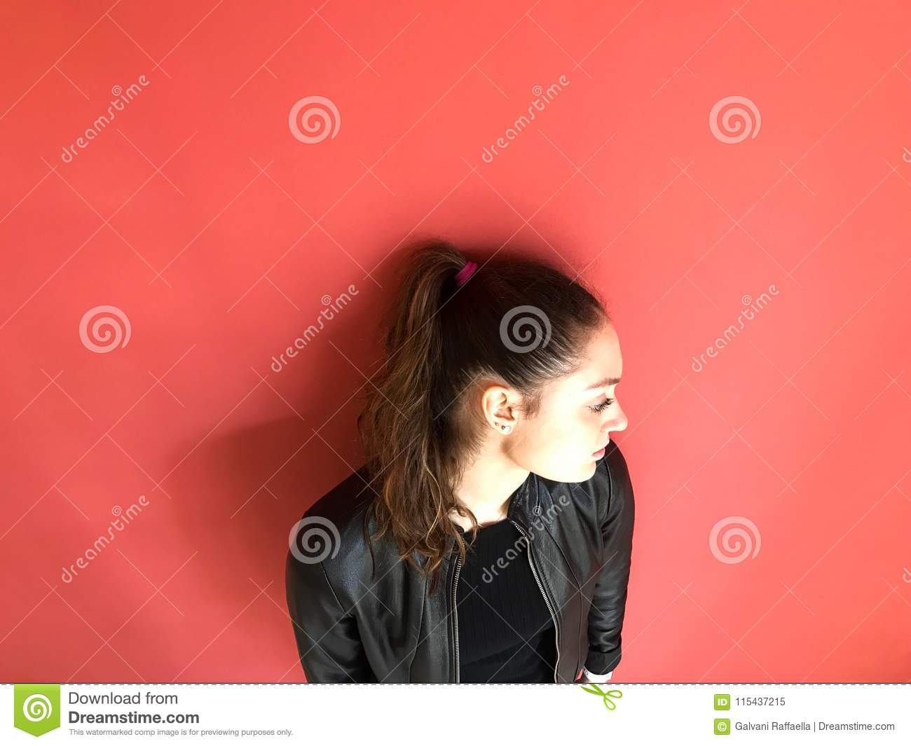 Young woman with ponytail portrait, coral color background