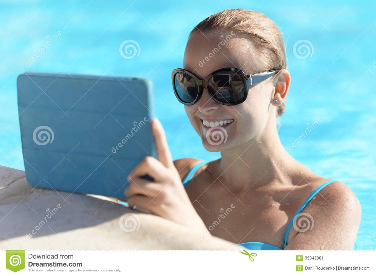 Young Woman In A Pool Using Tablet Computer Stock Photo