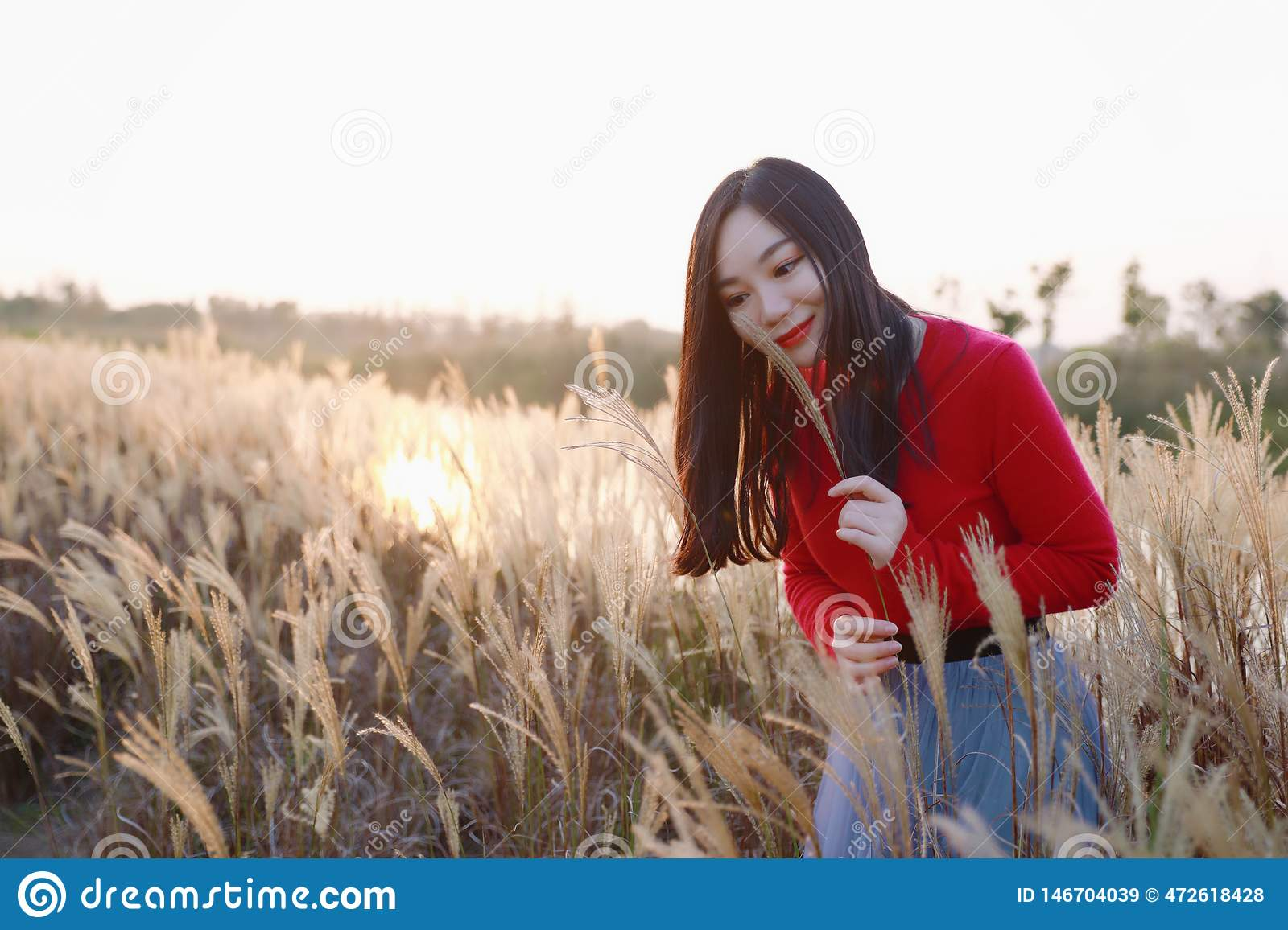 Enjoy in autumn sun , Young pretty woman stand on the grass and smiling at autumn sunset. Nature, natural.