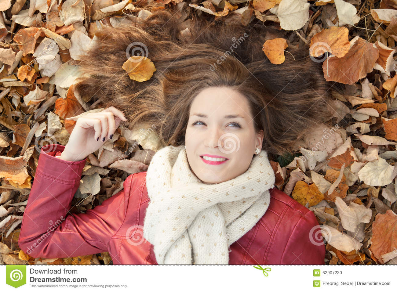 Young woman portrait lying on leaves, top view