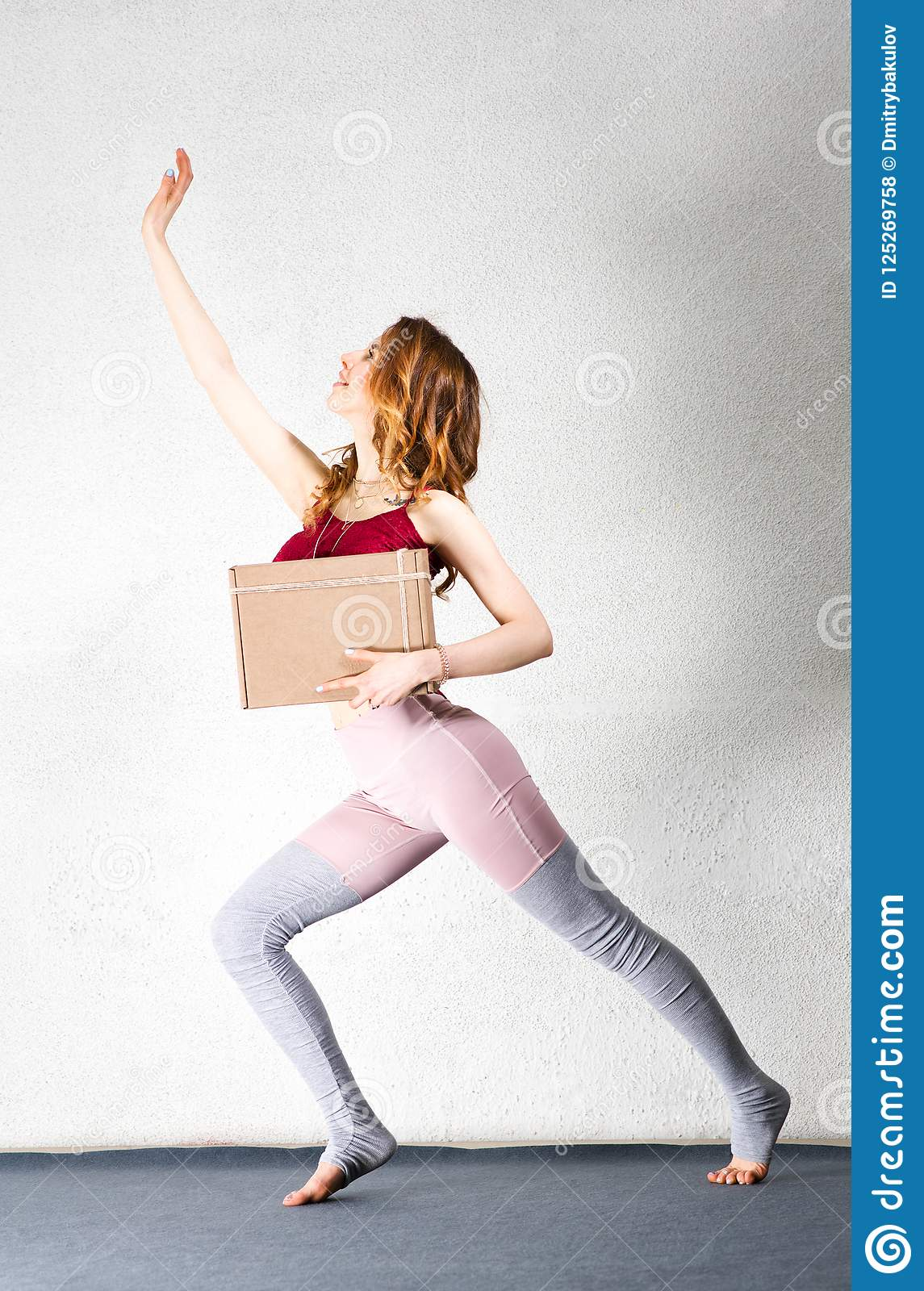 Young woman posing with a box in her hands. Package for yoga classes