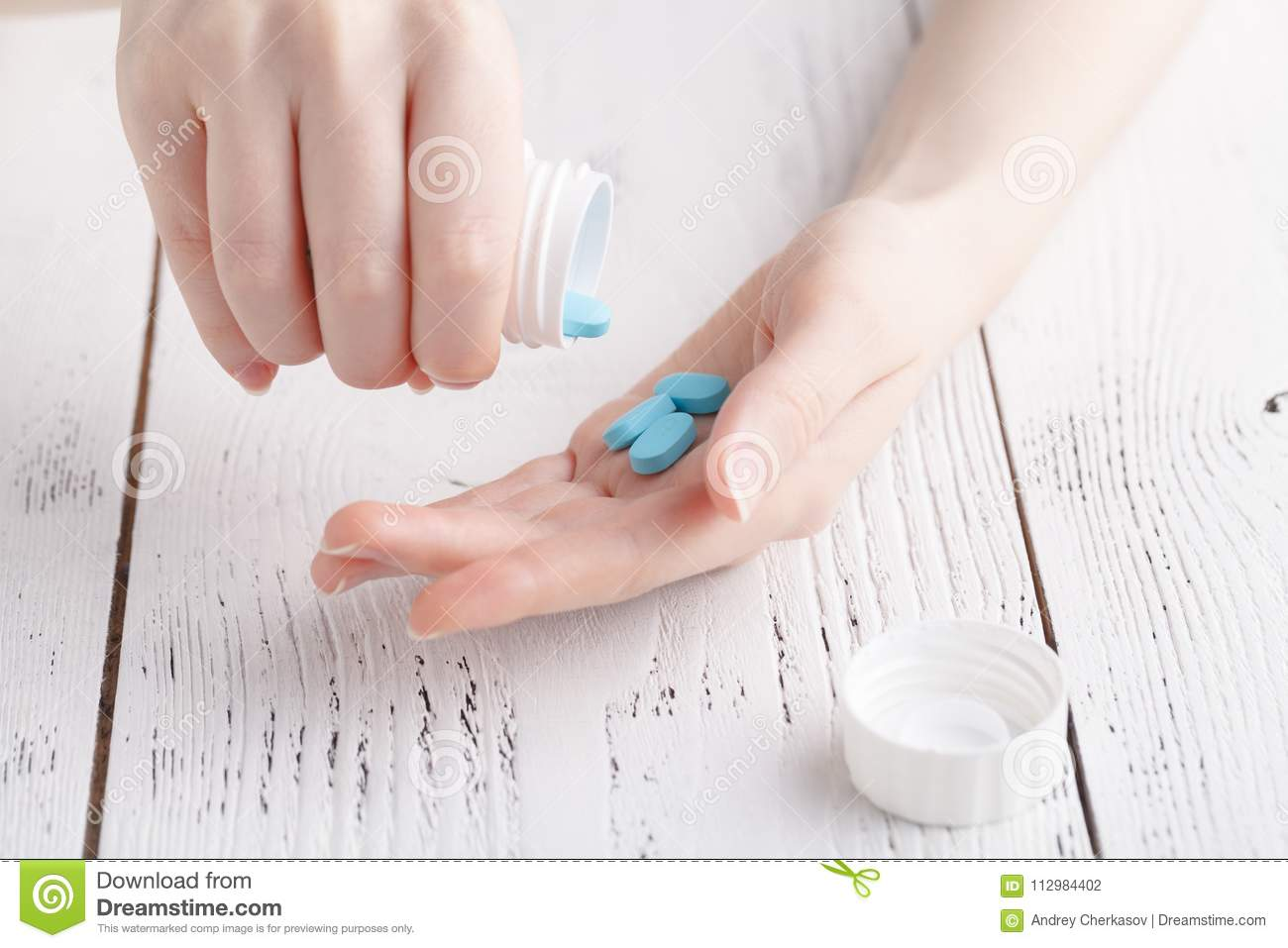 Young woman pours out medicine into her hand