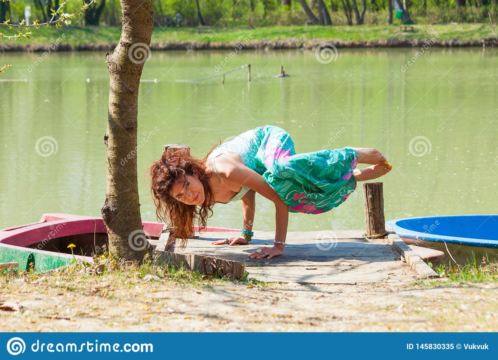 Young woman practice yoga outdoor by the lake balance pose on hands healthy lifestyle concept