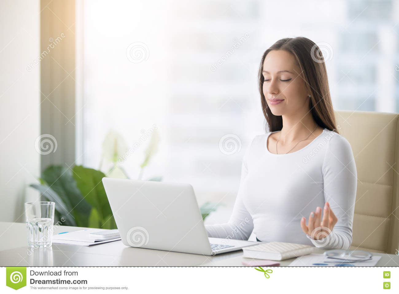 Young woman practicing meditation at the office desk
