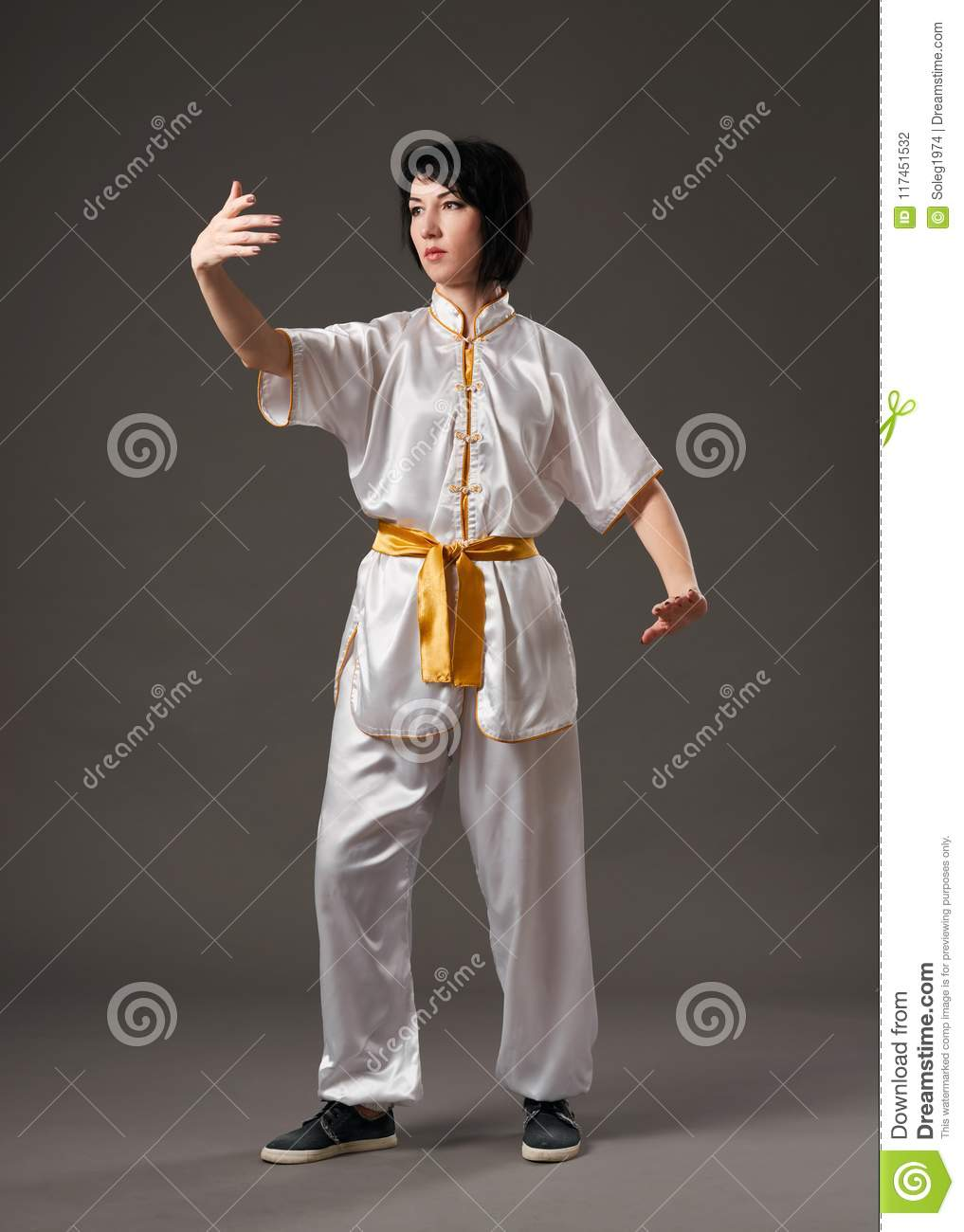 Young woman practicing tai chi chuan. Chinese management skill Qi`s energy. Gray background, studio shoot.