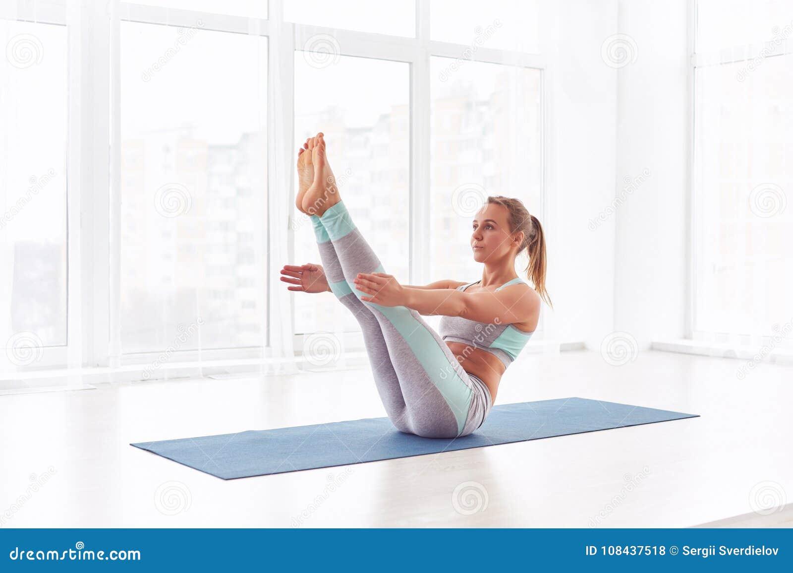 Young Woman Practicing Yoga, Sitting In Paripurna Navasana ...