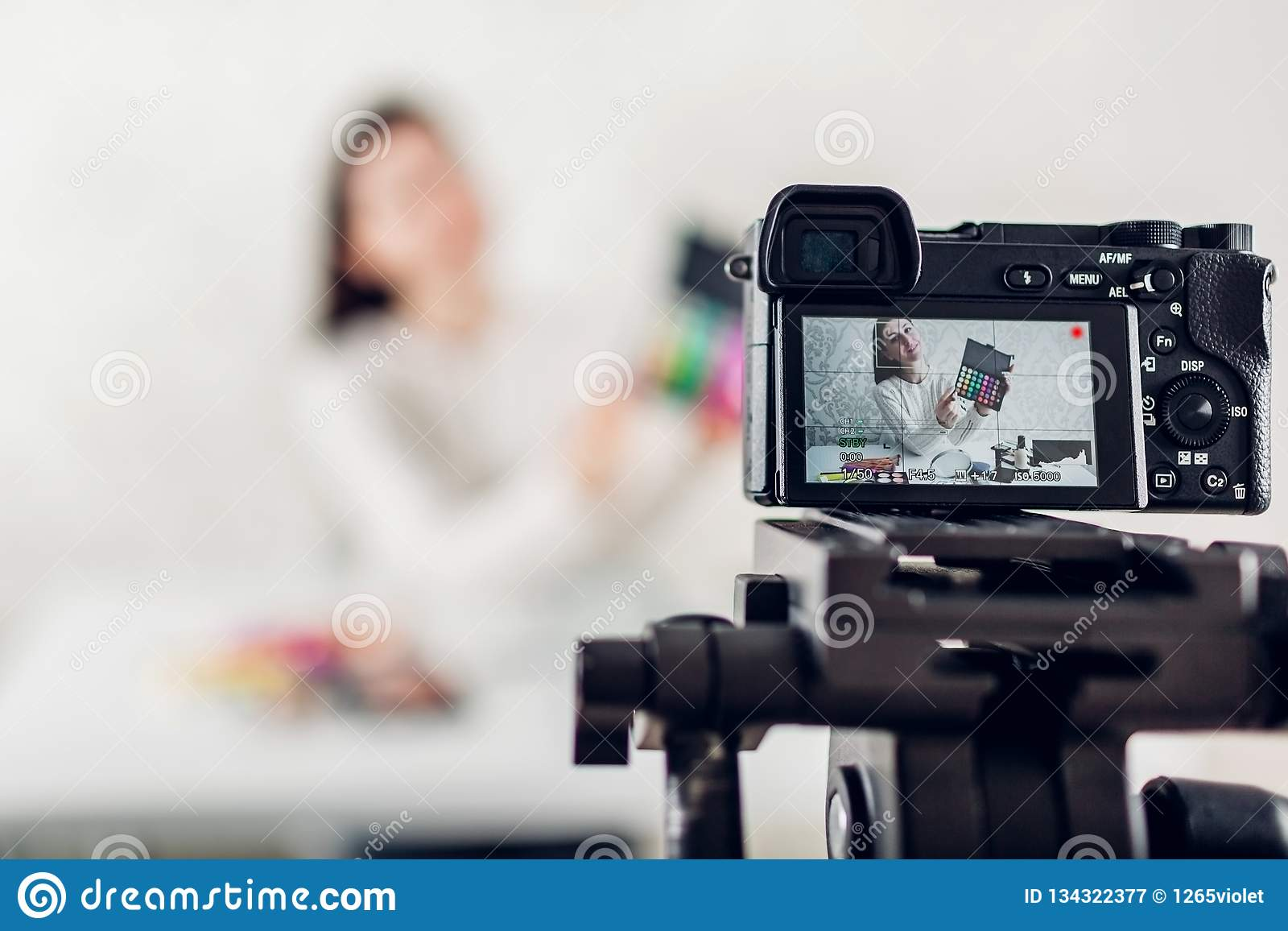 Young woman professional beauty vlogger or blogger recording make up tutorial using camera and tripod
