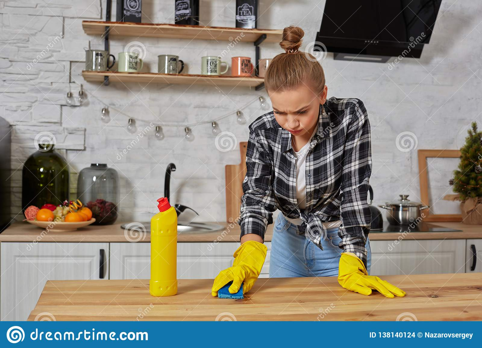 Young woman in protective gloves wipes a table in the kitchen with a rag