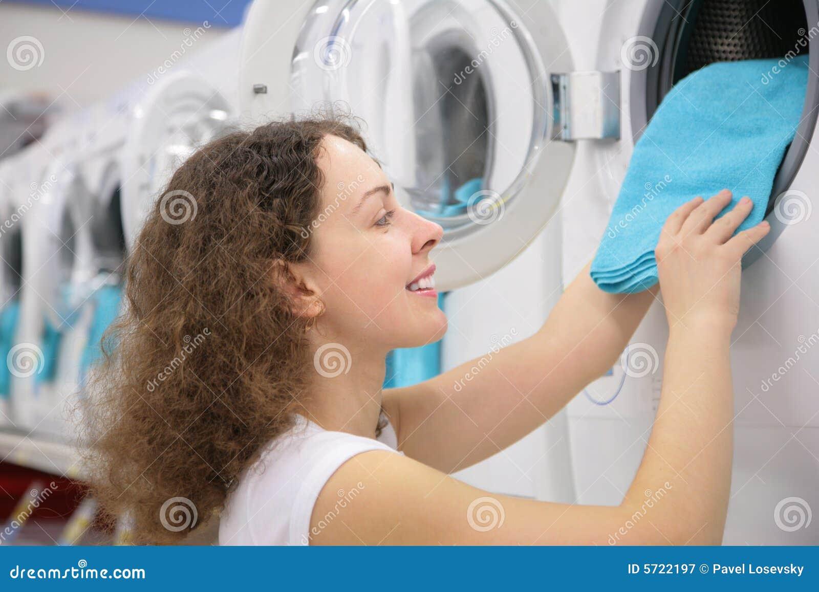 Young woman puts linen in washing machine in shop