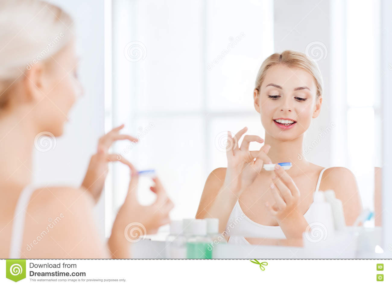 Young Woman Putting On Contact Lenses At Bathroom Stock