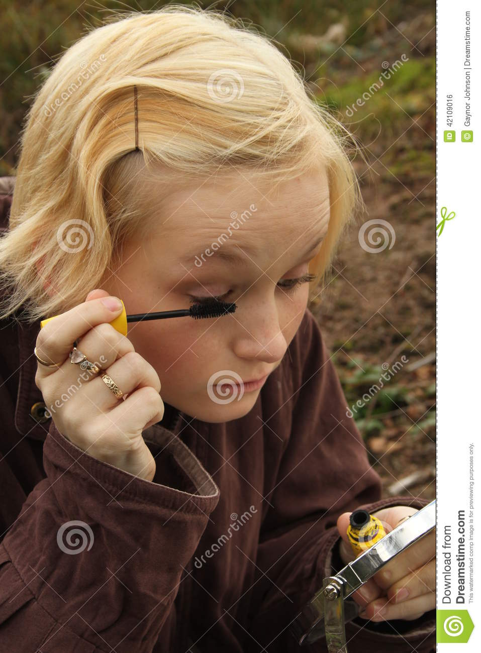 Young woman putting on make-up outdoors