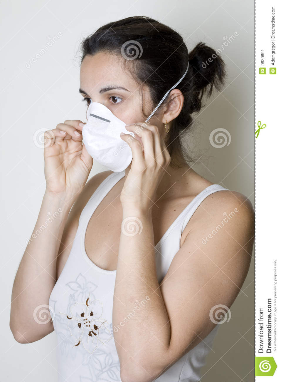 Young Woman Putting On A Mask Against Swine Flu Stock