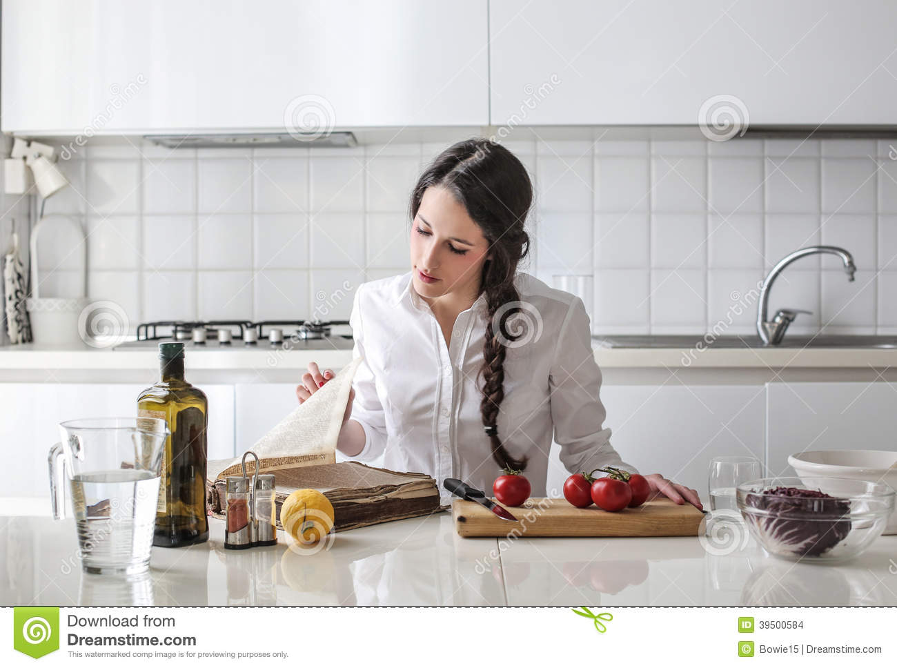 Young woman reading a cook book