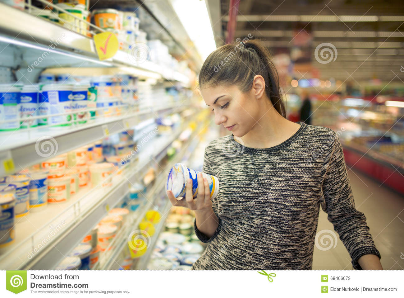 Young woman reading ingredients,declaration or expiration date on a diary product before buying it.Curious woman reading nutrition
