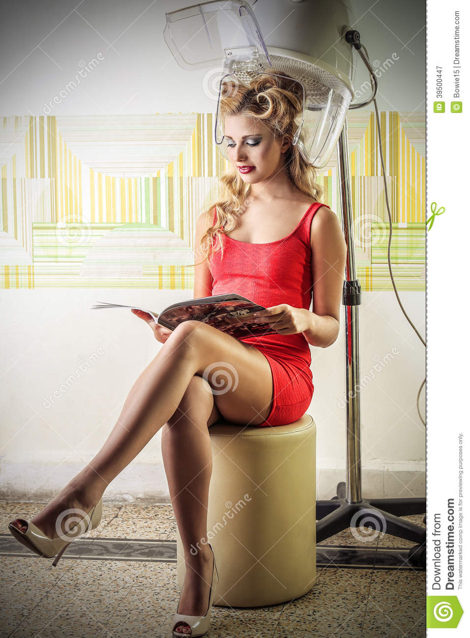Young woman reading a magazine at the hairdresser