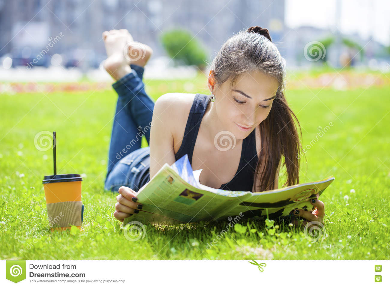 Young woman reading magazine lying on grass