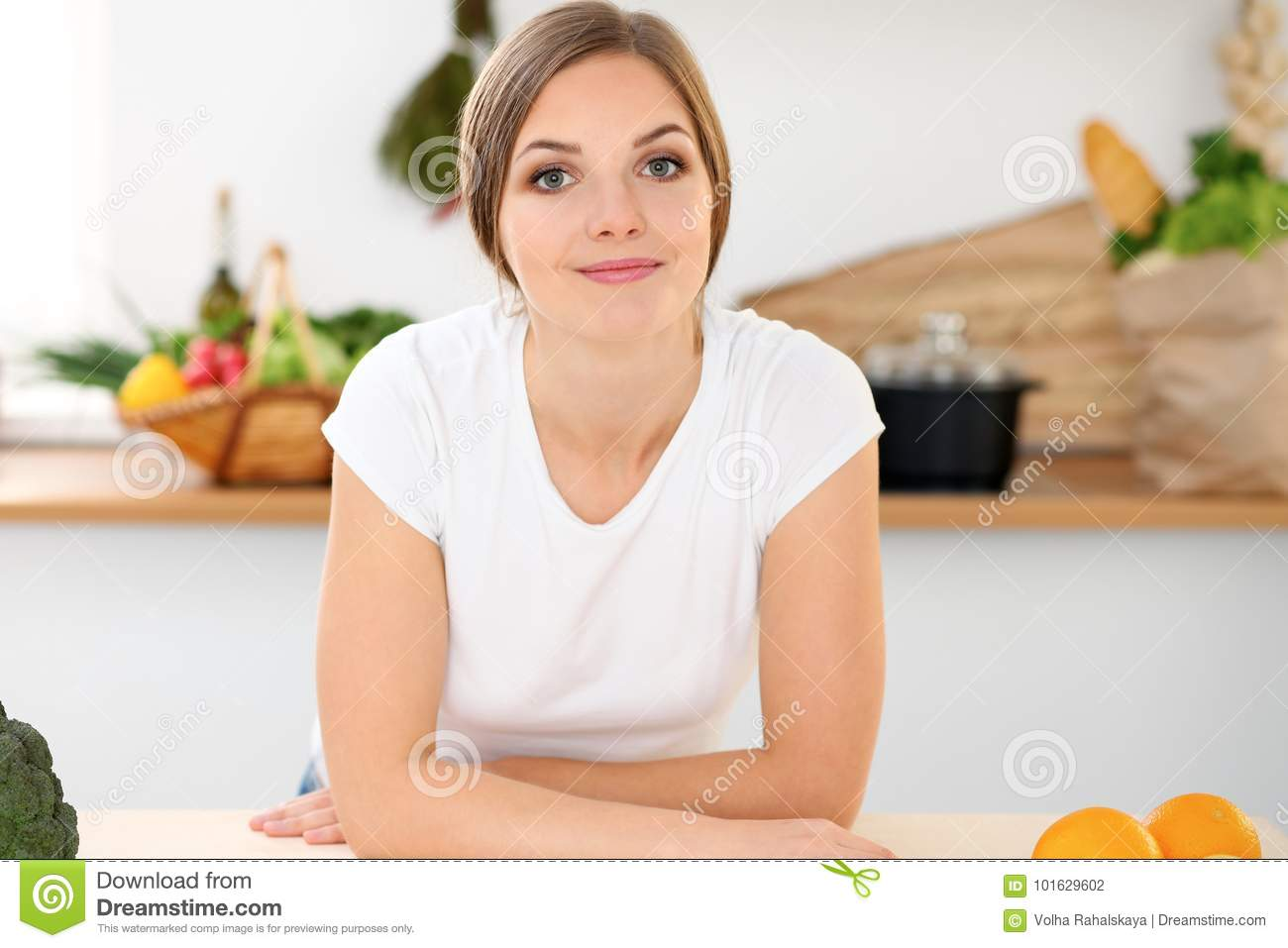 Young woman is ready for cooking in a kitchen. Housewife sitting at the table and looking at the camera.