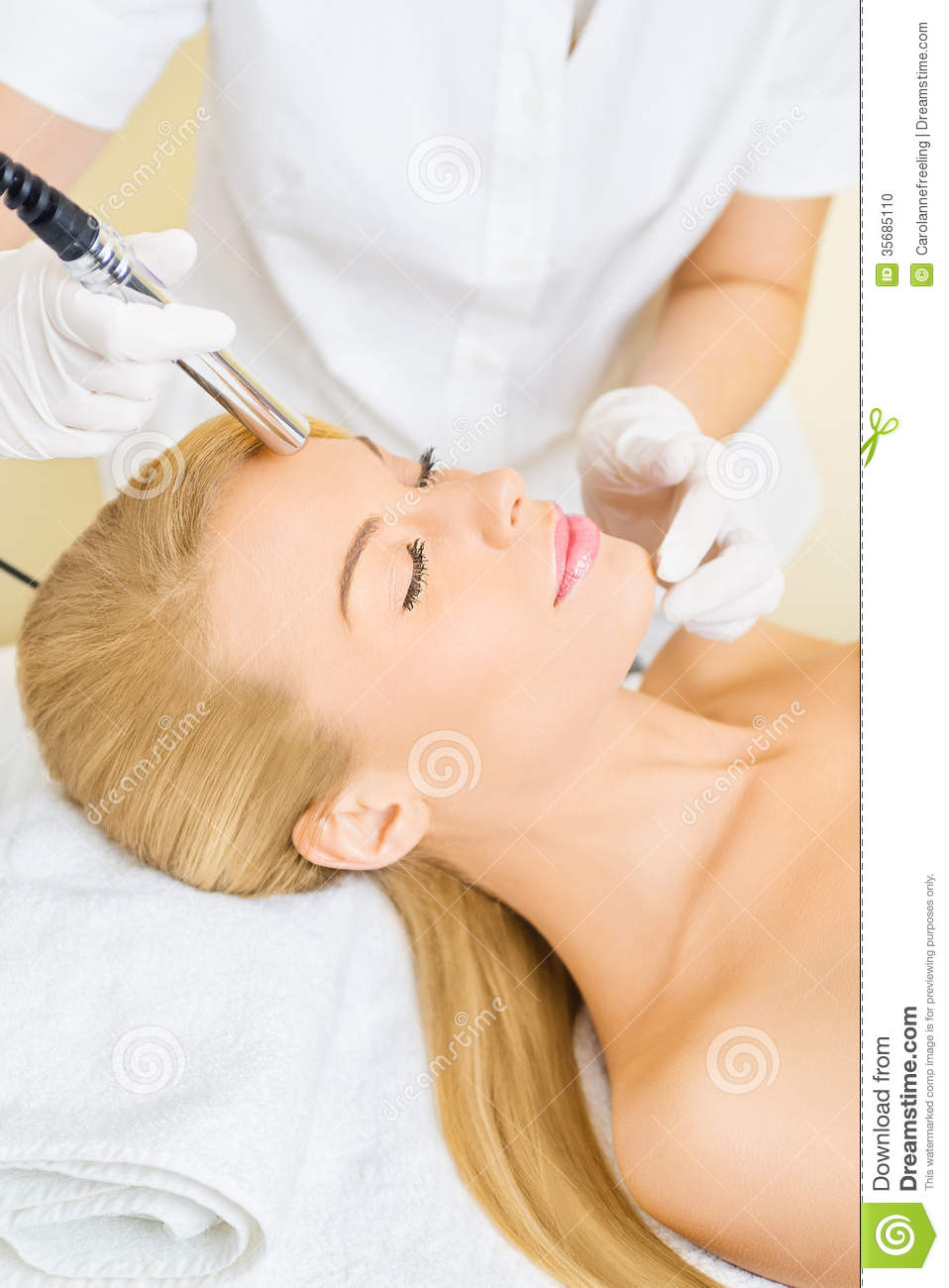 Young woman receiving microdermabrasion treatment stock for Salon younga