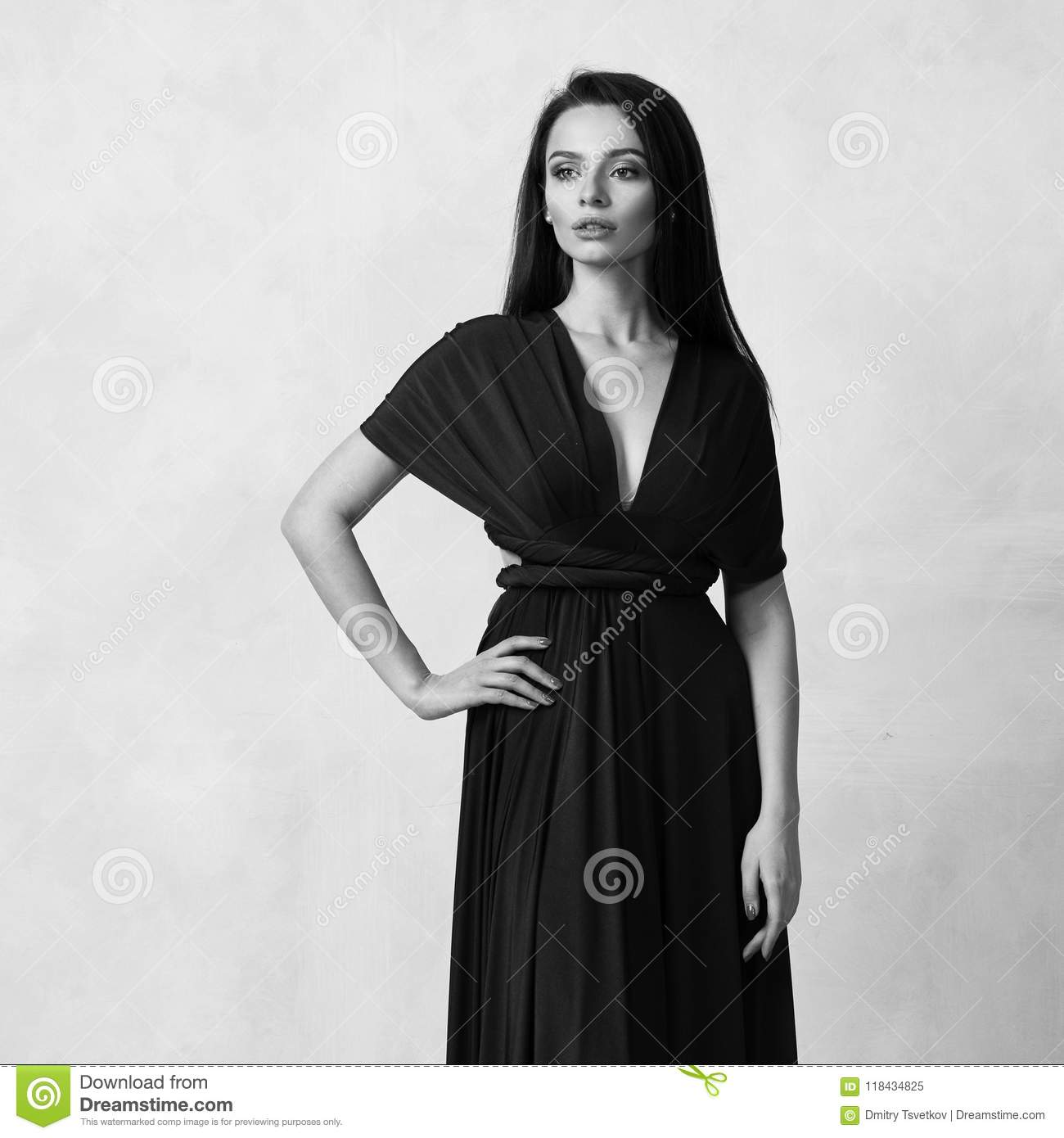 dd1119eee0 Beautiful long haired young woman dressed in stylish cherry red bandeau maxi  dress posing against white wall on background. Elegant brunette female  model ...