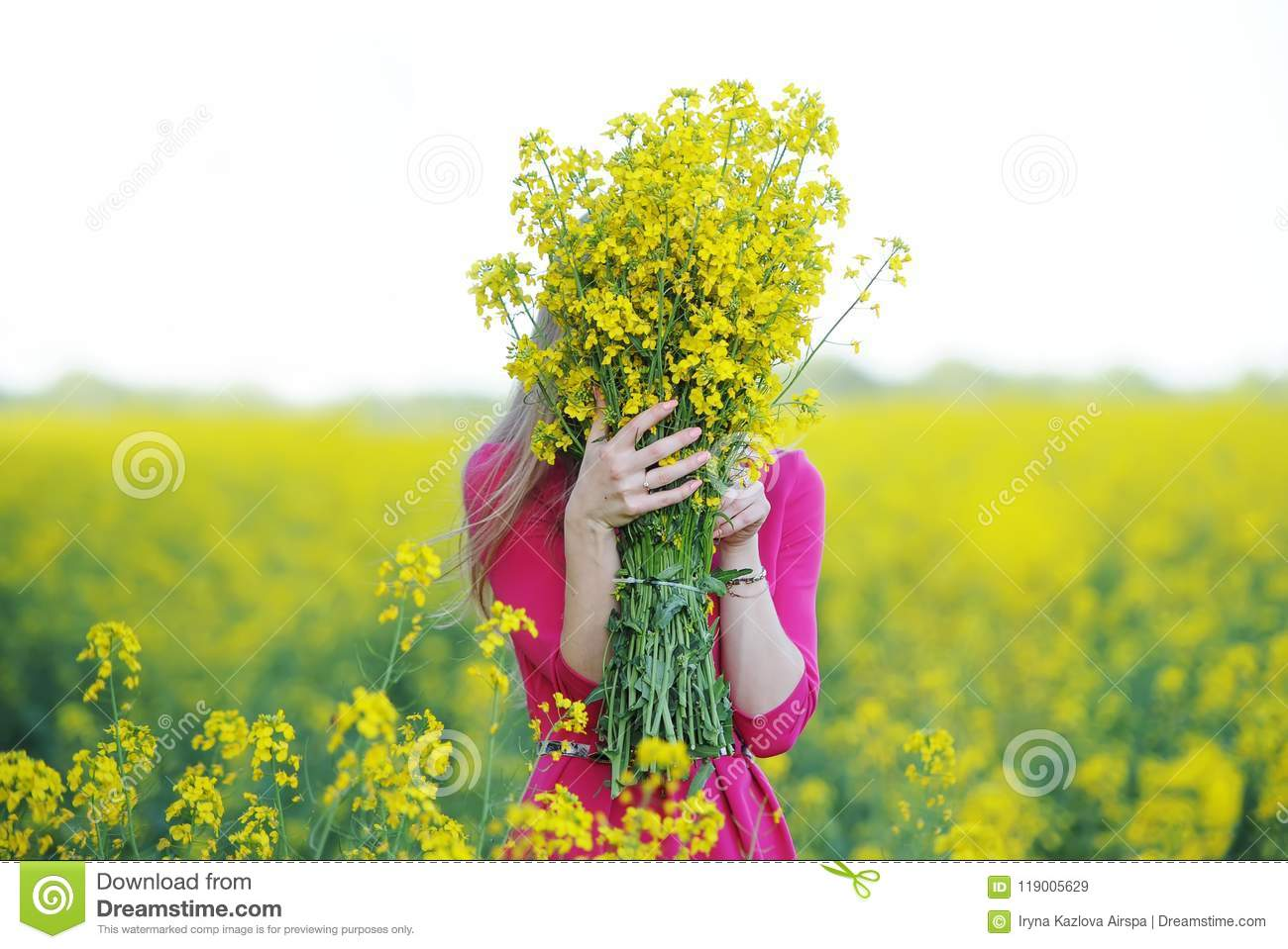 Young woman in a red dress has hidden a face behind a bouquet of yellow colors