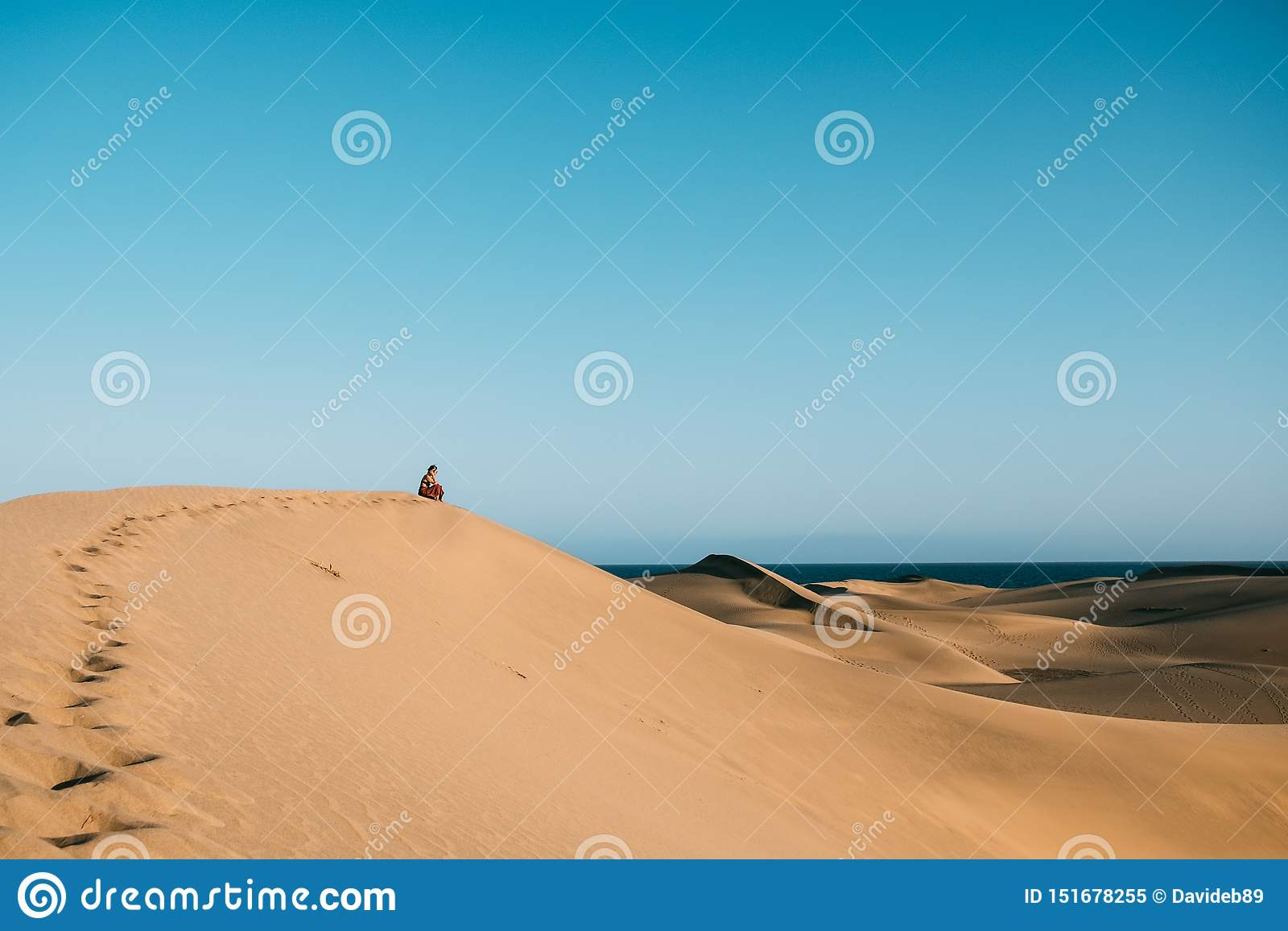 Young woman with red dress sit alone in the desert thinking and reflecting on top of dune as a metaphor of loneliness and
