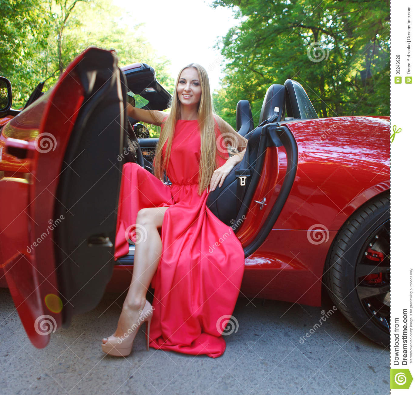Young Woman In Red Dress Siting In A Sports Car Stock