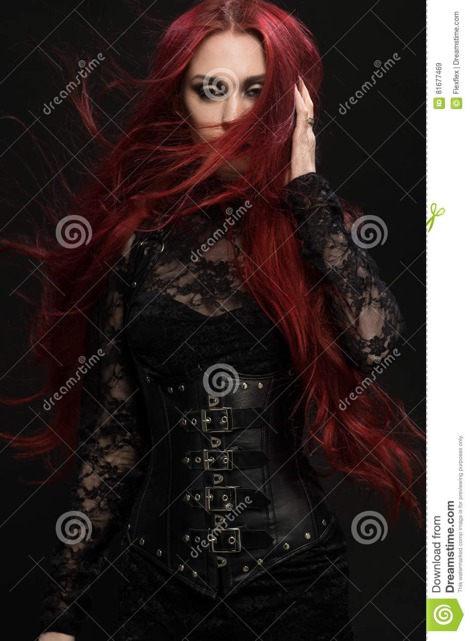 Young woman with red hair in black gothic costume