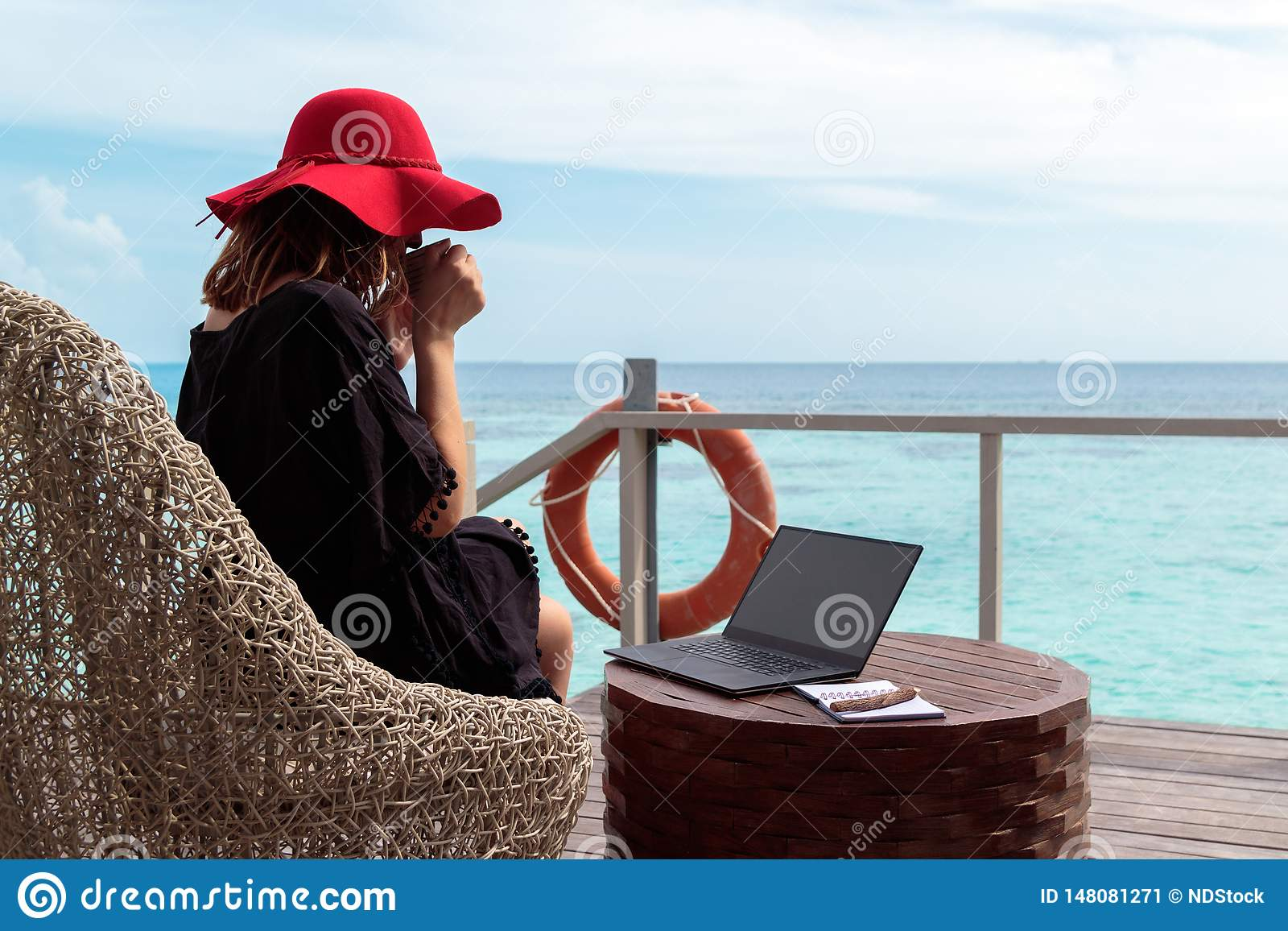 Young woman with red hat drinking coffee and working on a computer in a tropical destination