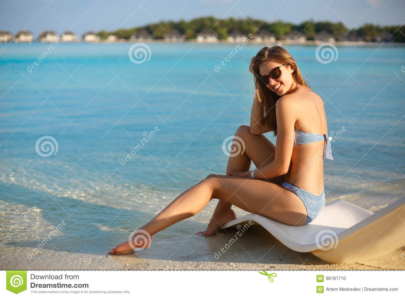 Young woman relaxing in a modern deck chair on a tropical beach with glasses on. Girl is sitting on a beach sun bed
