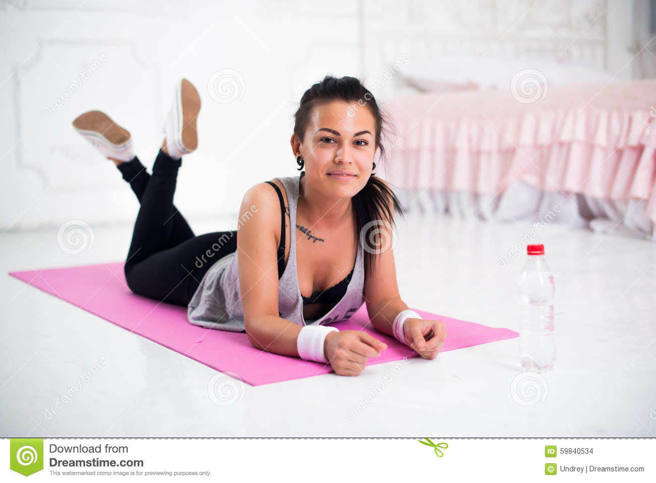 Young Woman Relaxing After Workout At Home Lying Stock