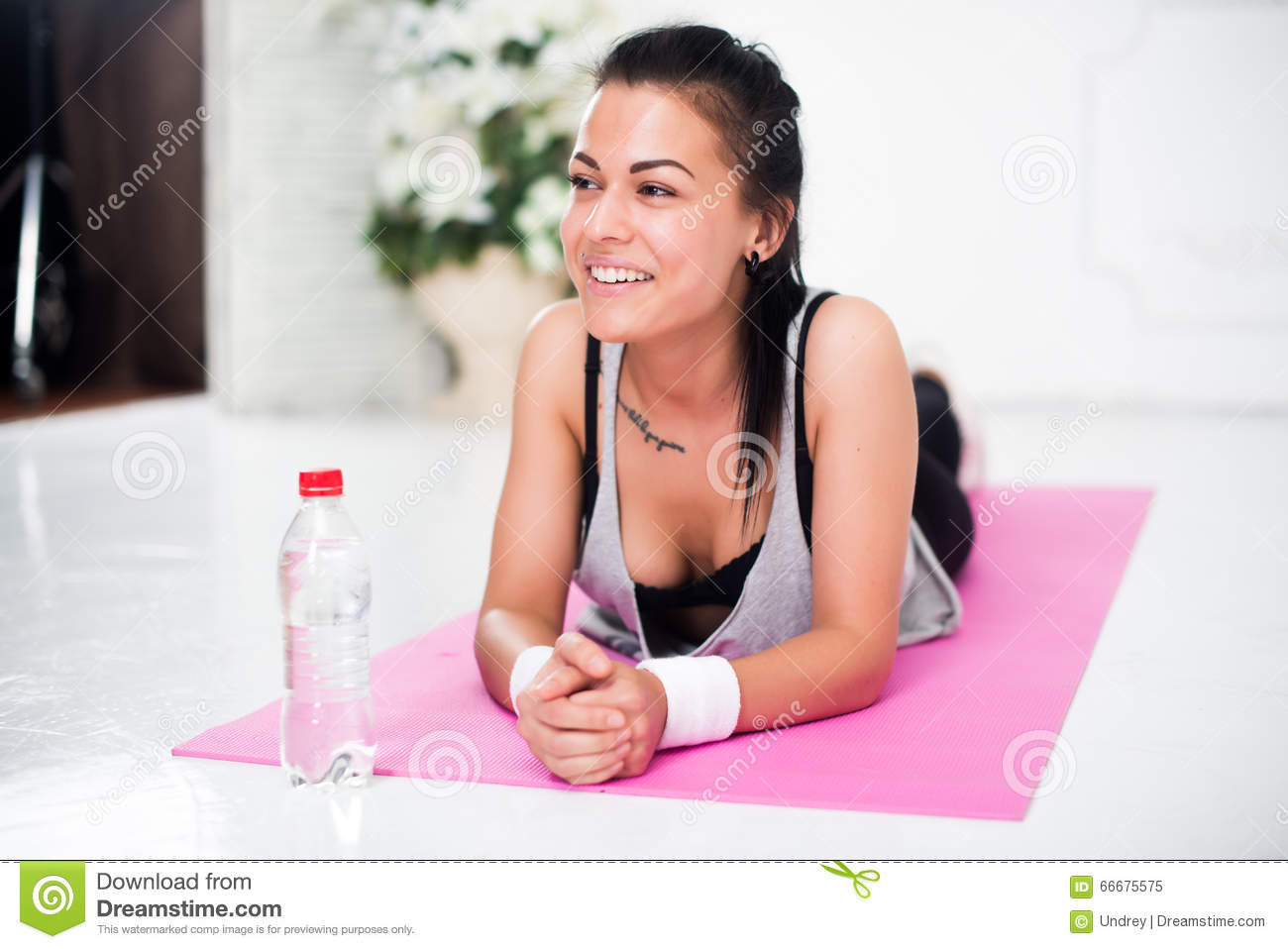Young woman relaxing after workout at home lying on yoga mat concept healthy lifestyle, training, diet