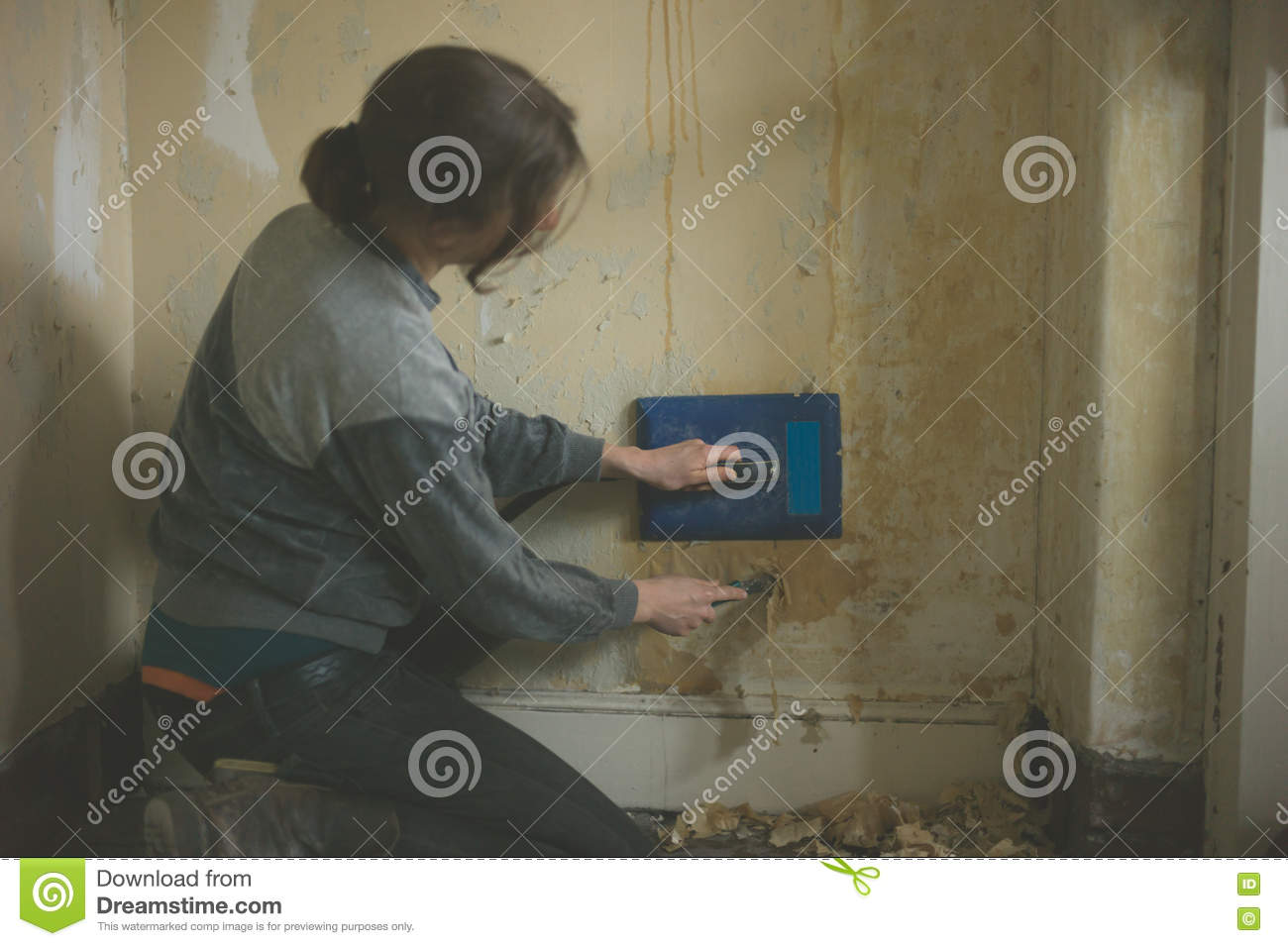 Young Woman Removing Wallpaper