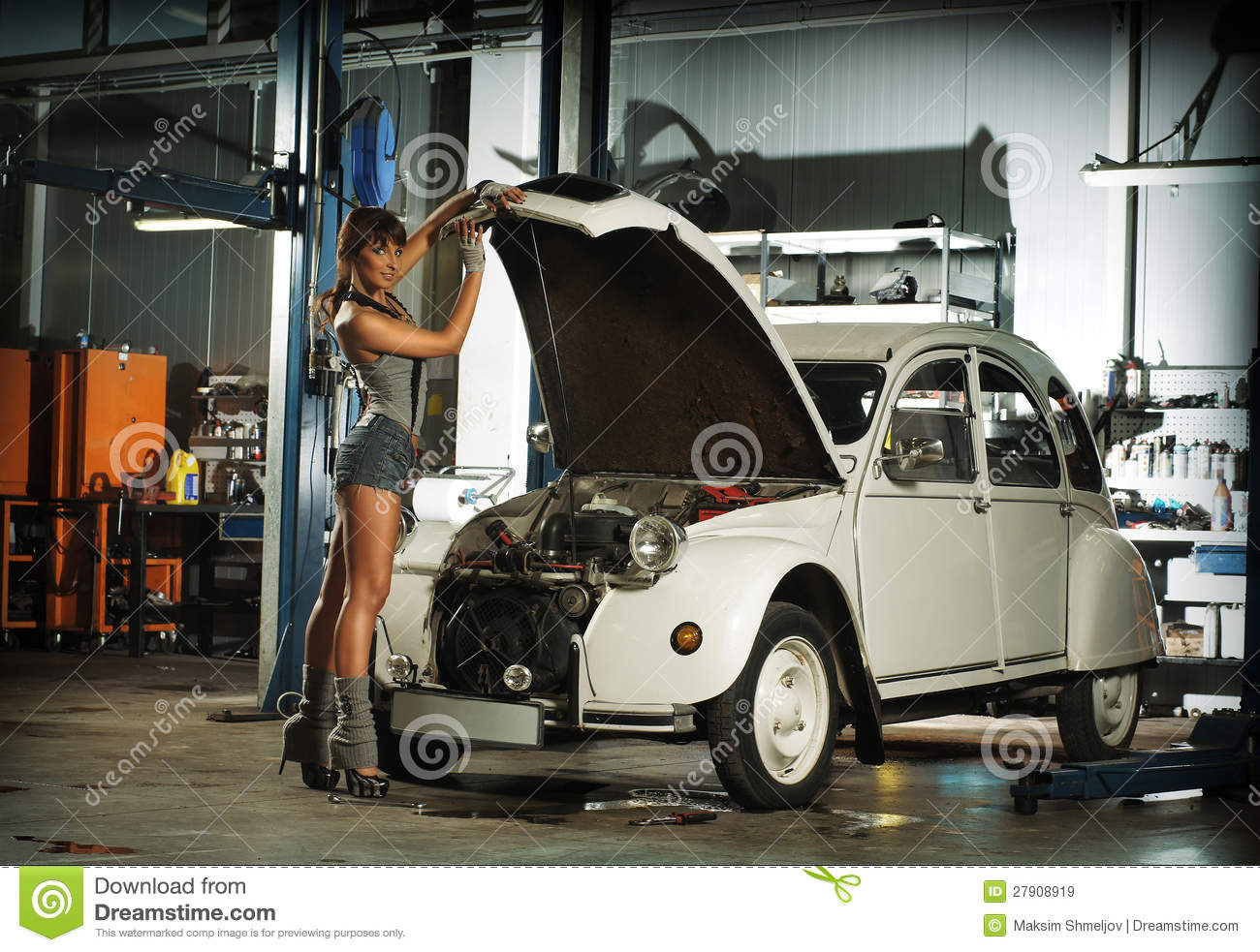 A young woman repairing a retro car in a garage stock for Car and garage