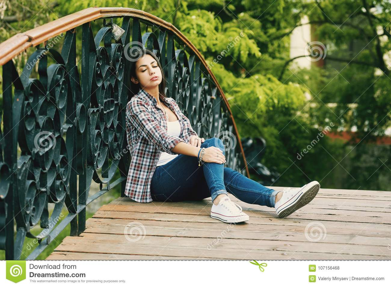 Young woman resting sitting on a wooden bridge