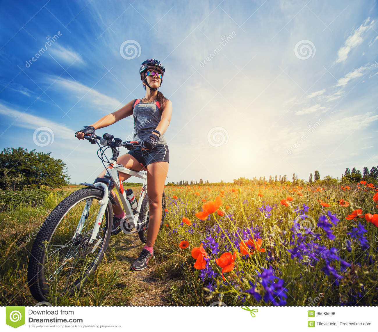 Young woman riding a bicycle on a blooming poppy meadow