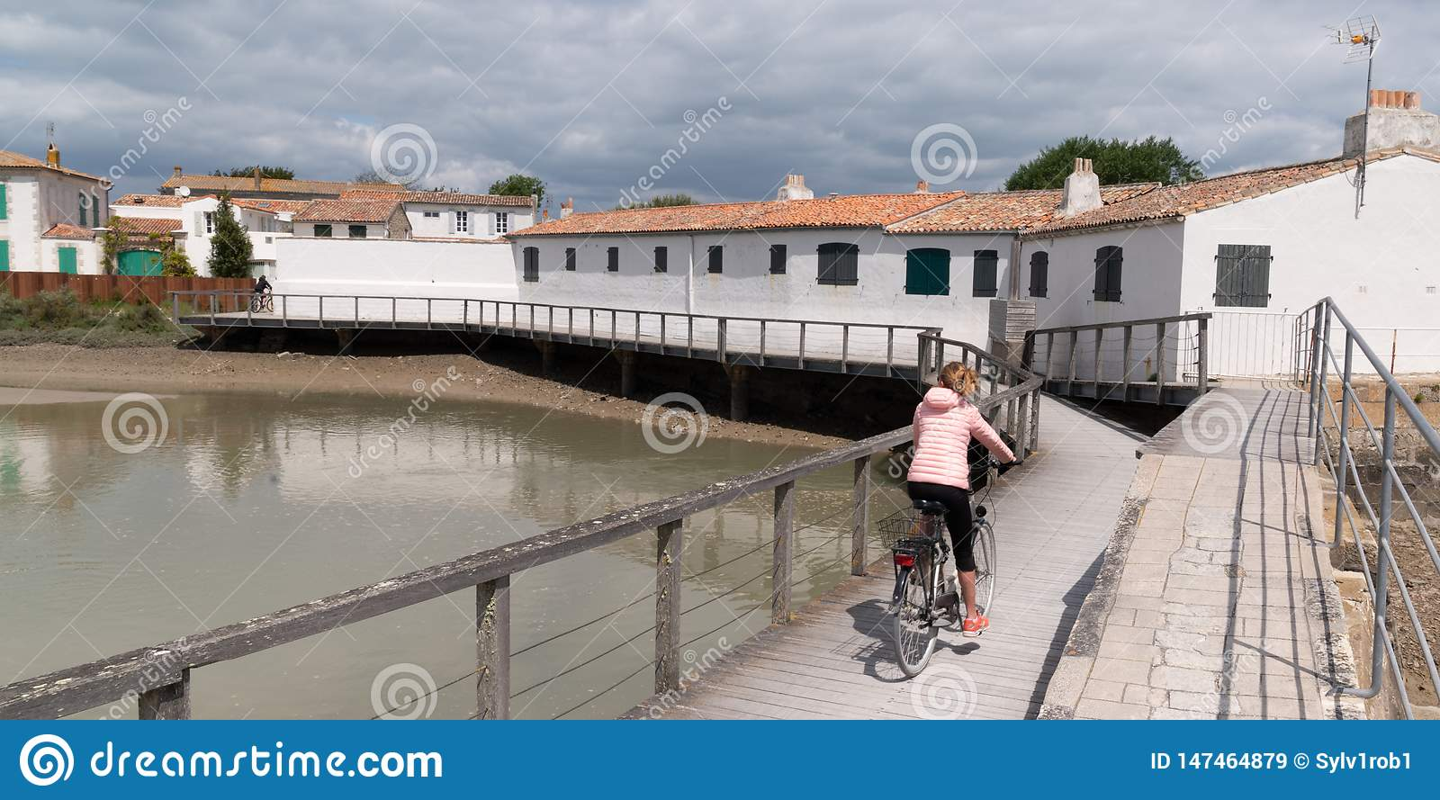 Young woman riding with bicycle on a wooden path to beach in Summer sunny day on island ile de Re in France