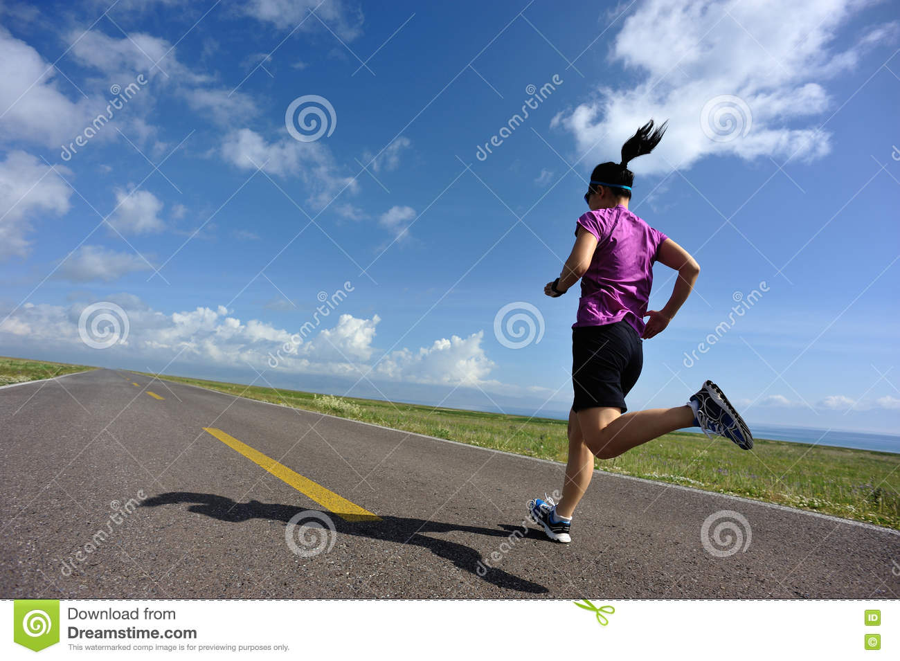 young woman runner running on beautiful road
