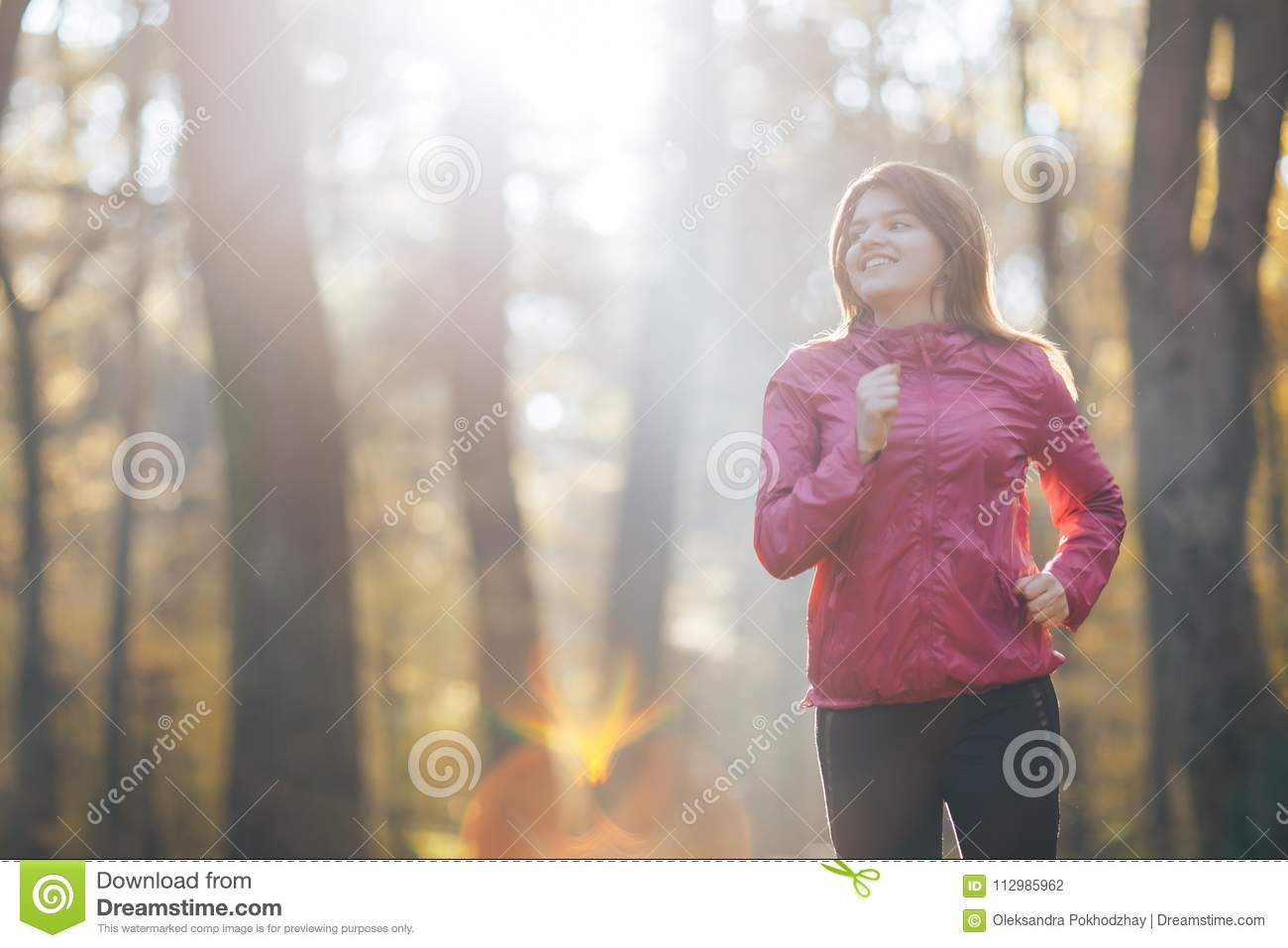 Young woman running during autumn forest