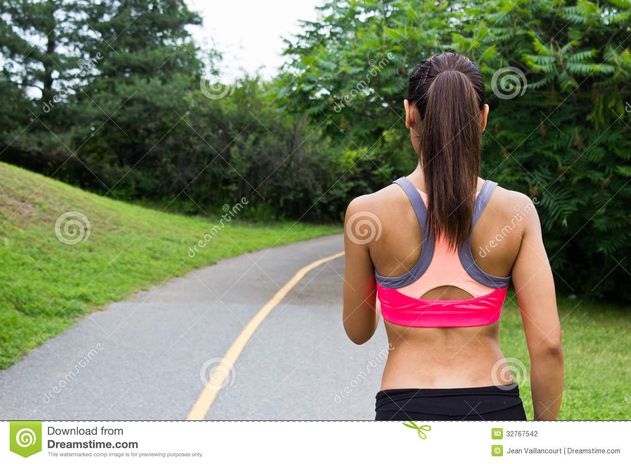 Young woman running on the jogging trail