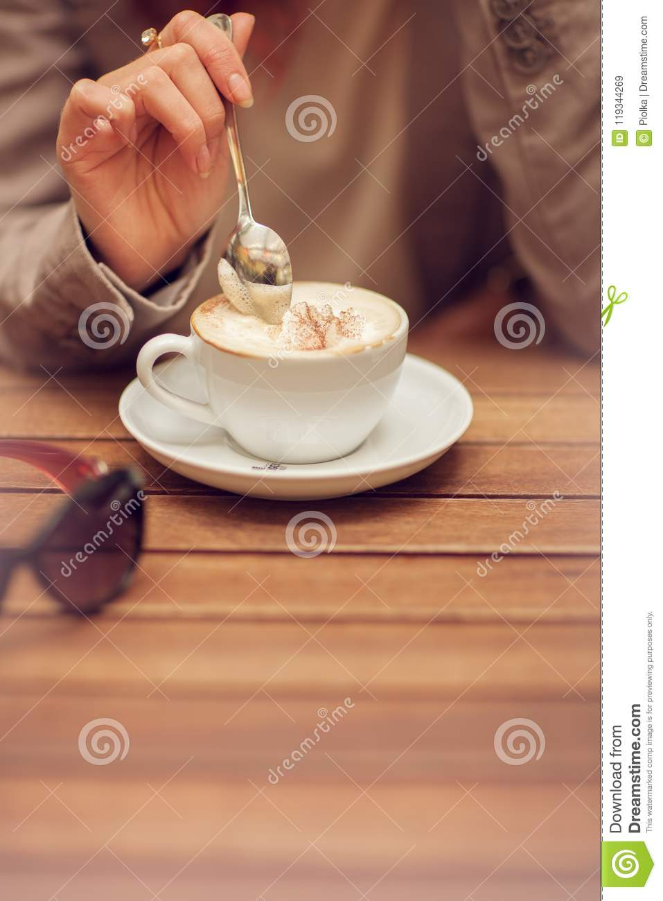 Young woman`s hand holding a spoon, stir a cup of coffee in a street cafe on a wooden table