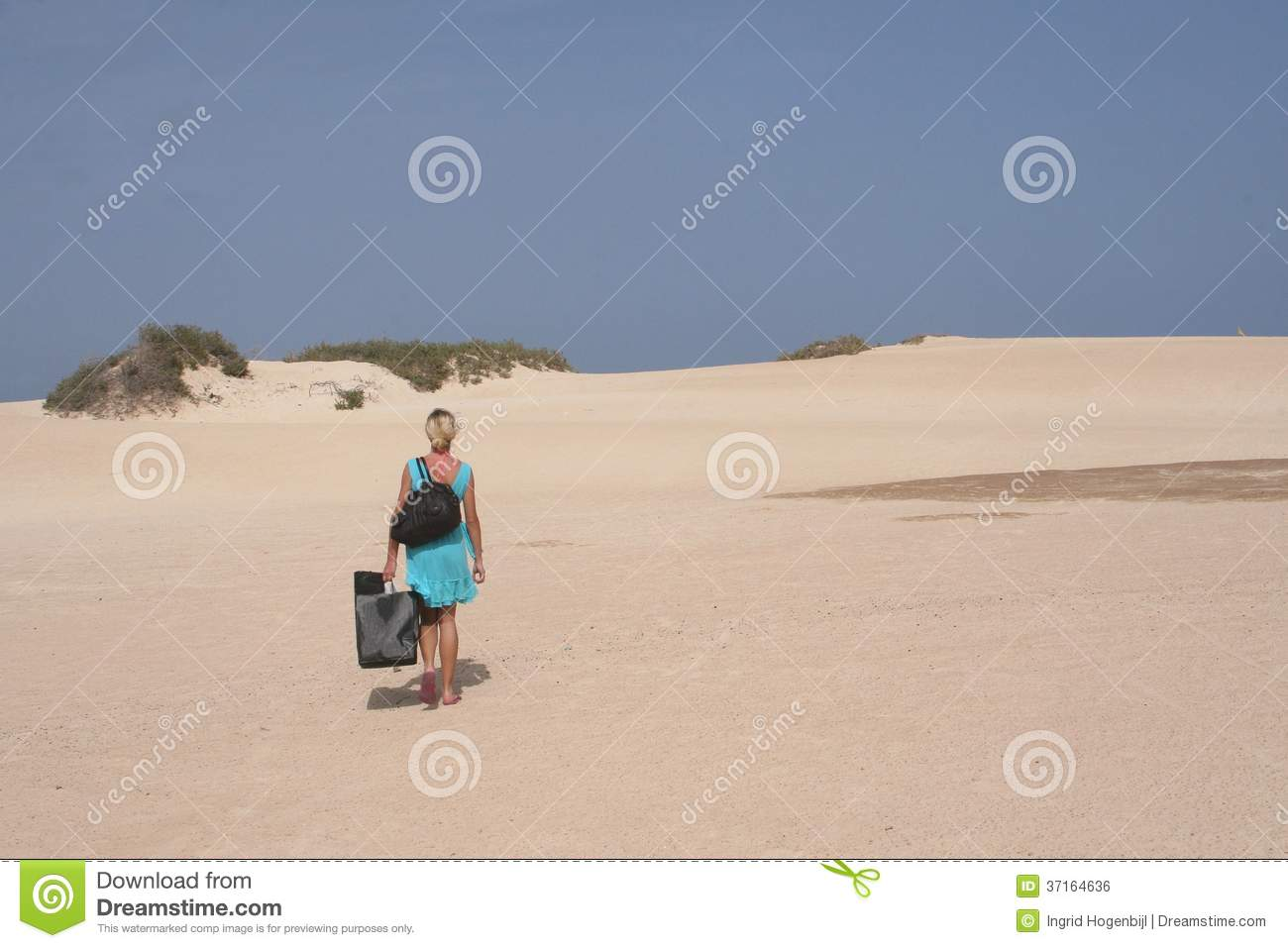Young Woman With Bags Is Hiking In Sand Dunes Of Desert