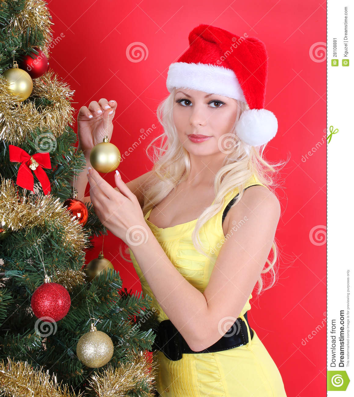 Young Woman In Santa Hat Decorating Christmas Tree Over