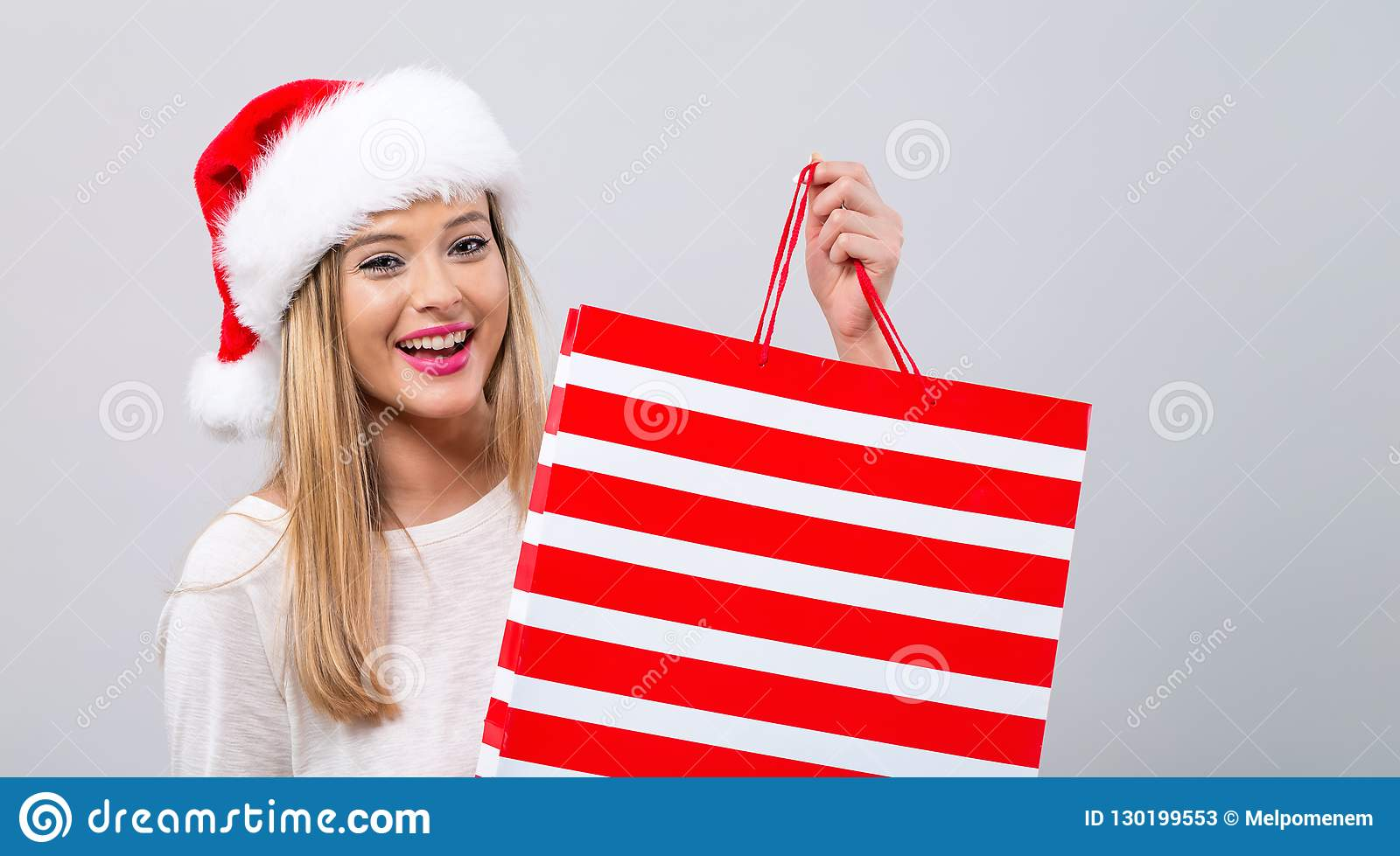 e44db540683b8 Young Woman With Santa Hat Holding A Shopping Bag Stock Image ...