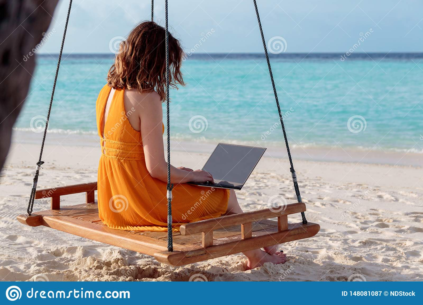 Young woman seated on a swing and working with his laptop. Clear blue tropical water as background