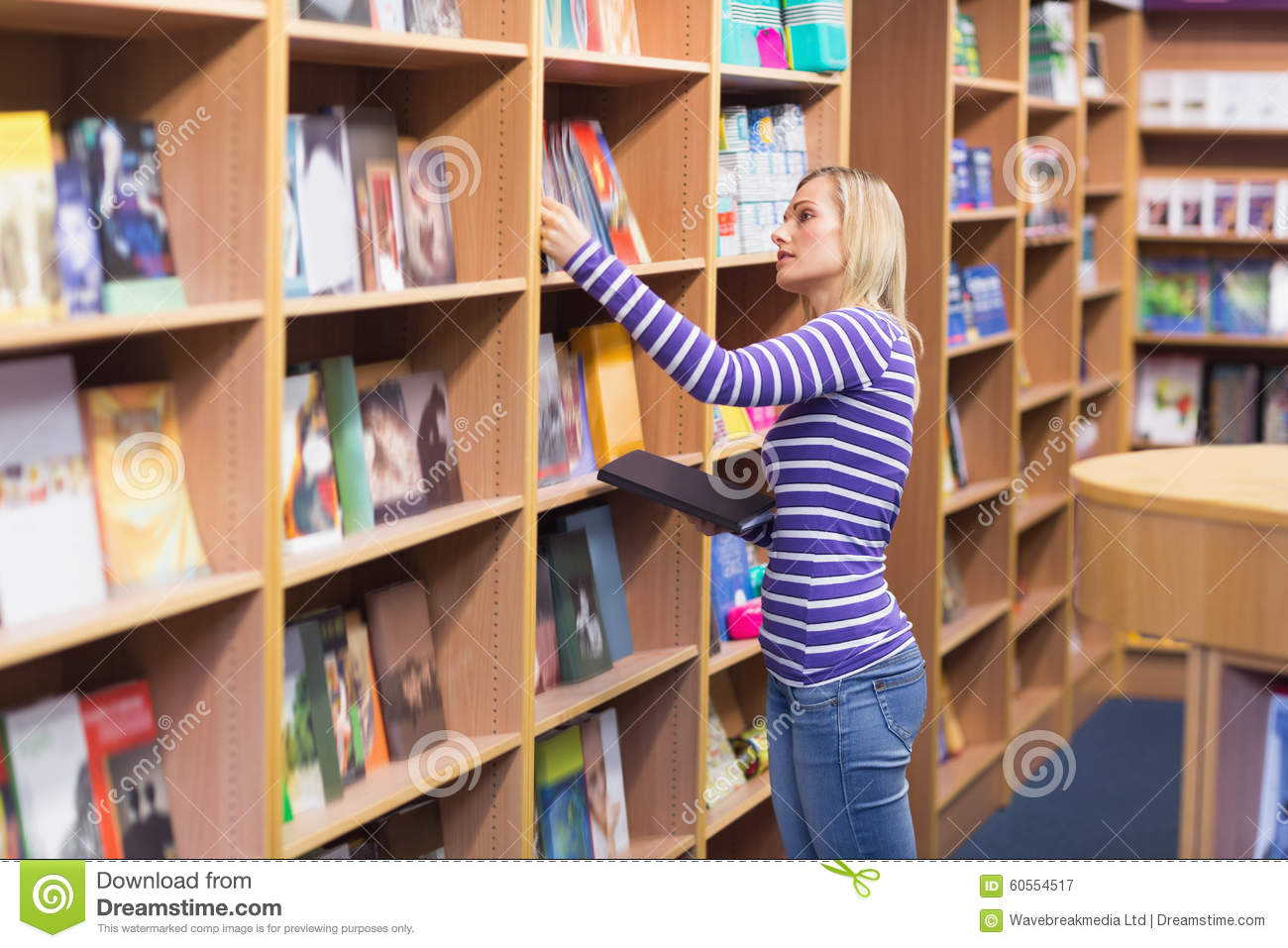 Young Woman Selecting Book From Bookshelf Download Preview